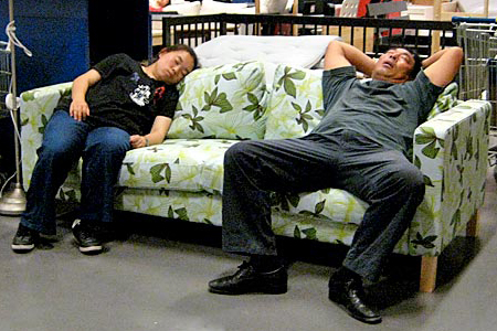 Two visitors to Beijing's IKEA enjoy a nap on a display sofa. (David Pierson / Los Angeles Times)
